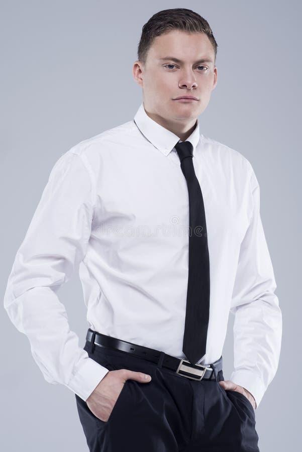 Jeune homme bel dans une chemise avec un lien sur un fond gris-clair images stock