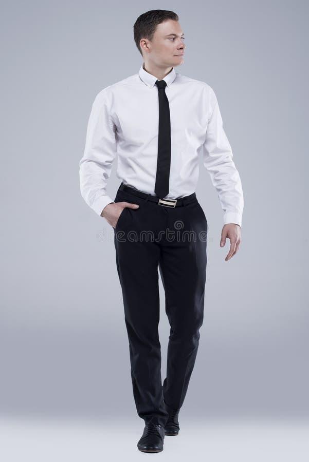 Jeune homme bel dans une chemise avec un lien sur un fond gris-clair image libre de droits