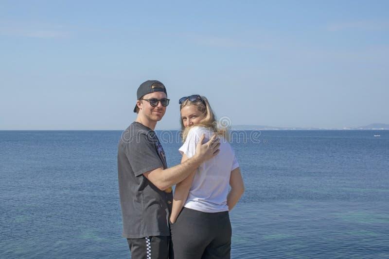 Jeune homme bel de sourire avec le chapeau vers l'arrière et le beau regard blond de femme photographie stock