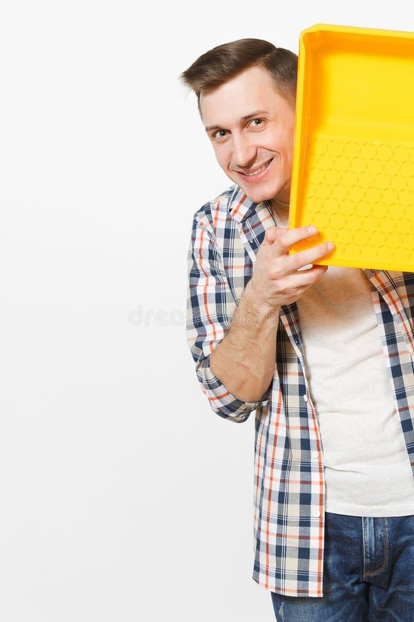 Jeune homme bel de sourire dans des vêtements sport jugeant le plateau de peinture d'isolement sur le fond blanc Instruments, acc images stock