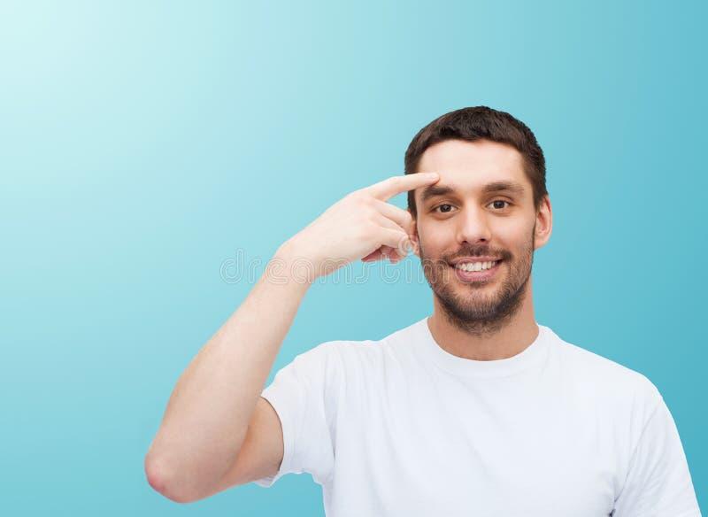 Jeune homme bel de sourire indiquant le front photos libres de droits