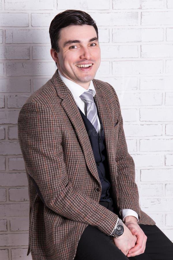 Jeune homme bel heureux au-dessus du mur blanc image stock