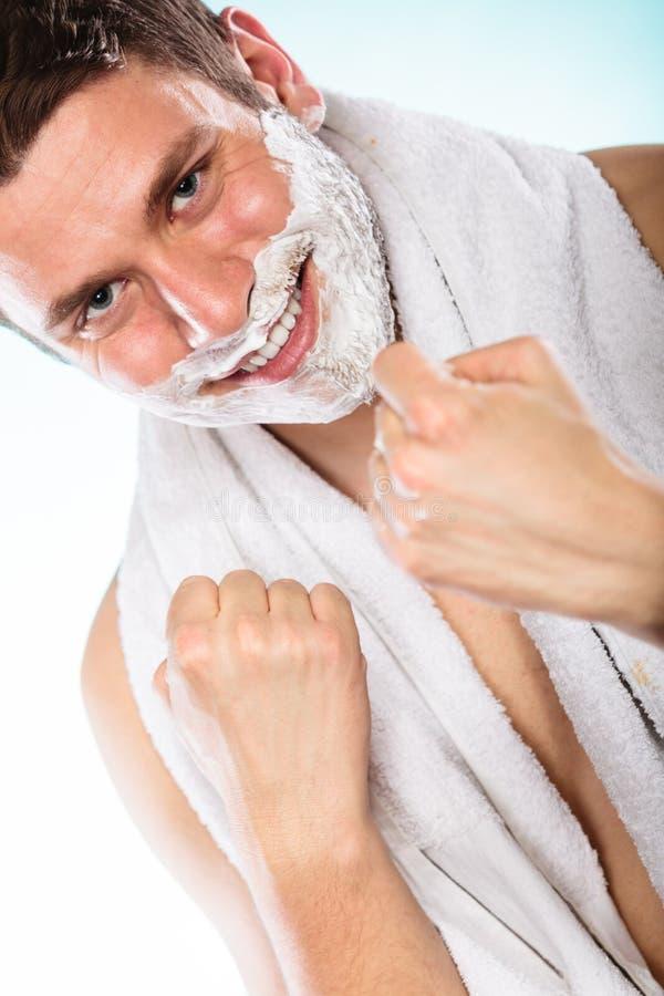 Jeune homme bel heureux avec la mousse de crème à raser photo stock