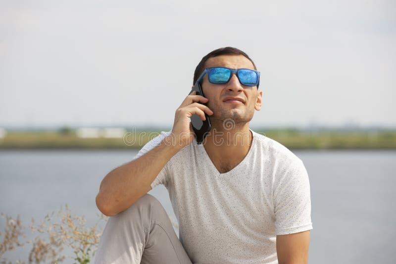 Jeune homme bel heureux s'asseyant sur le banc dehors et ? l'aide du smartphone photos stock