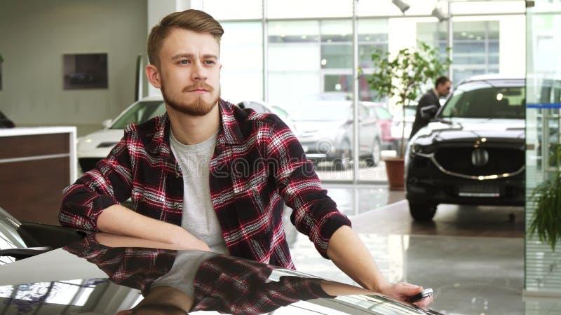 Jeune homme bel montrant des clés de voiture à sa nouvelle automobile au salon de concessionnaire photographie stock