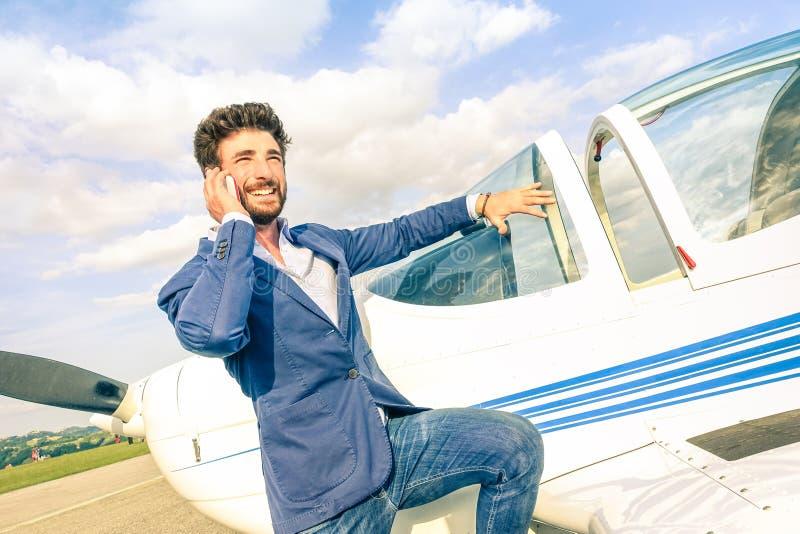 Jeune homme bel parlant avec le téléphone intelligent mobile à l'avion photos libres de droits