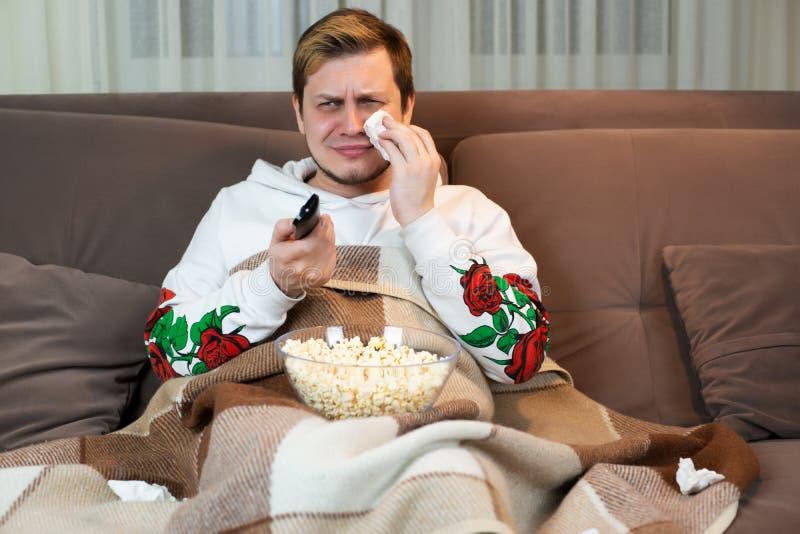 Jeune homme bel pleurant tout en observant touchant le film avec le maïs éclaté sur le sofa confortable photographie stock libre de droits