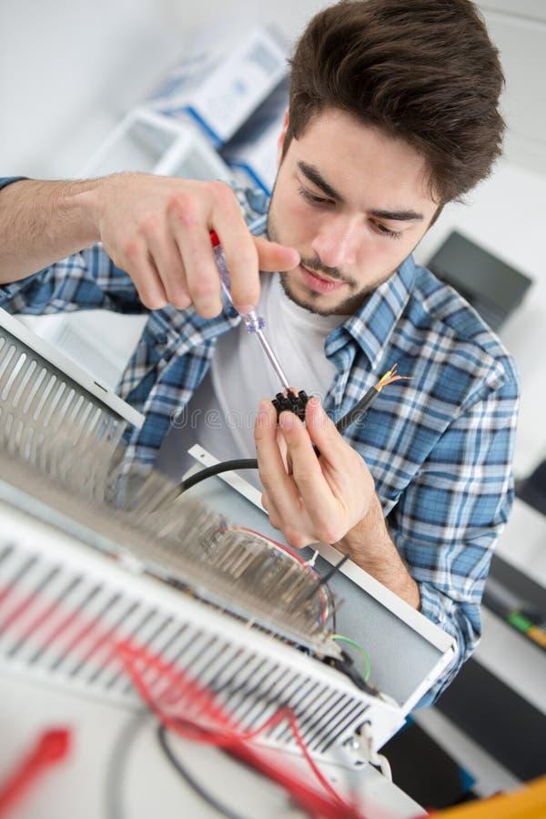 Jeune homme bel réparant le radiateur image stock