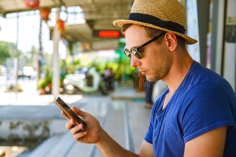 Jeune homme bel regardant vers le bas le t?l?phone portable avec le sourire images libres de droits
