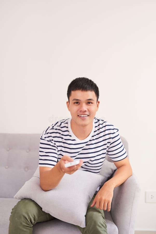 Jeune homme bel s'asseyant au sofa et à la TV de observation à la maison image stock