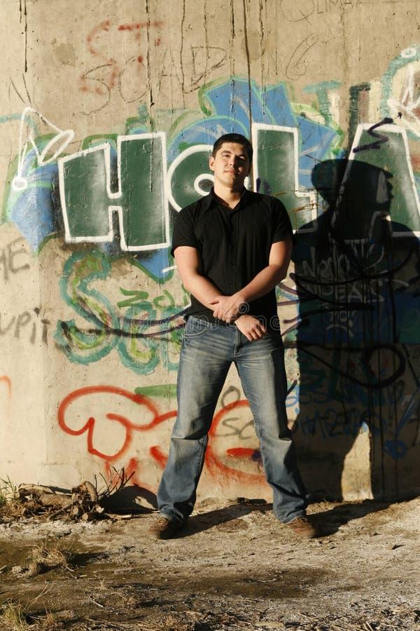 Jeune homme bel se tenant prêt le mur de graffiti image libre de droits