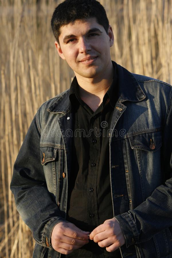 Jeune homme bel souriant modestement photo stock