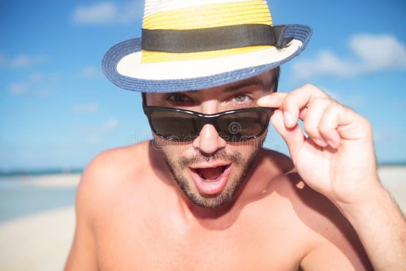 Jeune homme bel stupéfait sur la plage photos stock