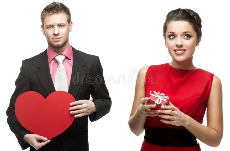 Jeune homme bel tenant le coeur rouge et femme de sourire tenant g images libres de droits