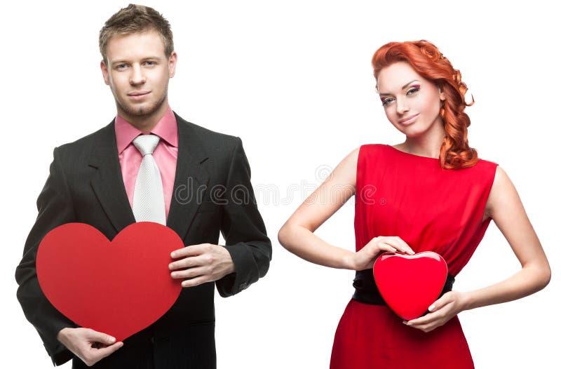 Jeune homme bel tenant le coeur rouge et femme gaie sur le blanc photo stock