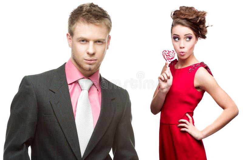 Jeune homme bel tenant le coeur rouge et femme gaie sur le blanc images libres de droits
