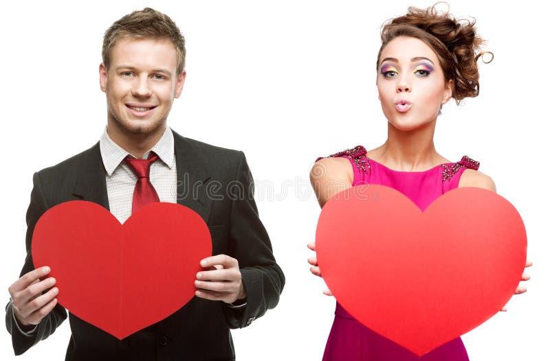 Jeune homme bel tenant le coeur rouge et femme gaie sur le blanc image stock