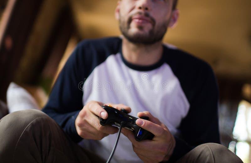 Jeune homme bel tenant le contrôleur de jeu jouant des jeux vidéo images stock