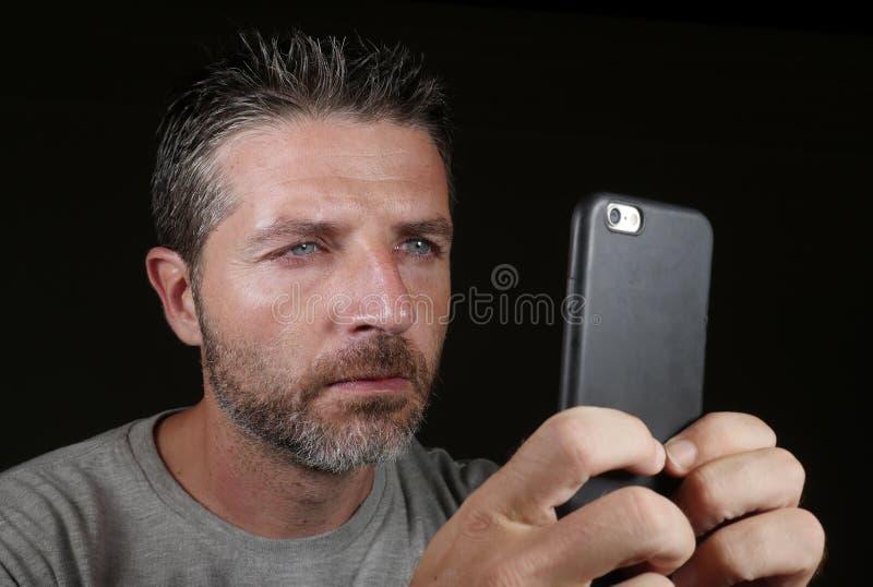 Jeune homme blanc attirant et sûr avec des yeux bleus utilisant l'appli ou l'Internet datant en ligne médias sociaux au téléphone images stock
