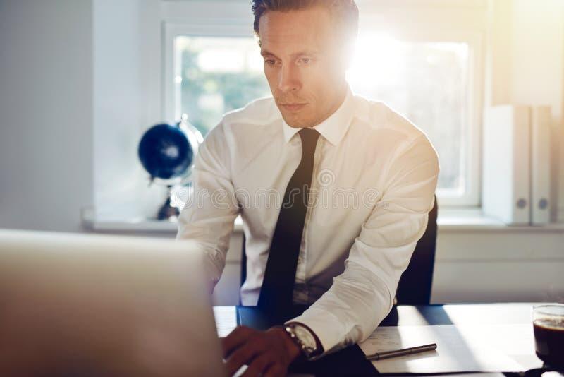 Jeune homme blanc d'affaires travaillant sur l'ordinateur photo libre de droits