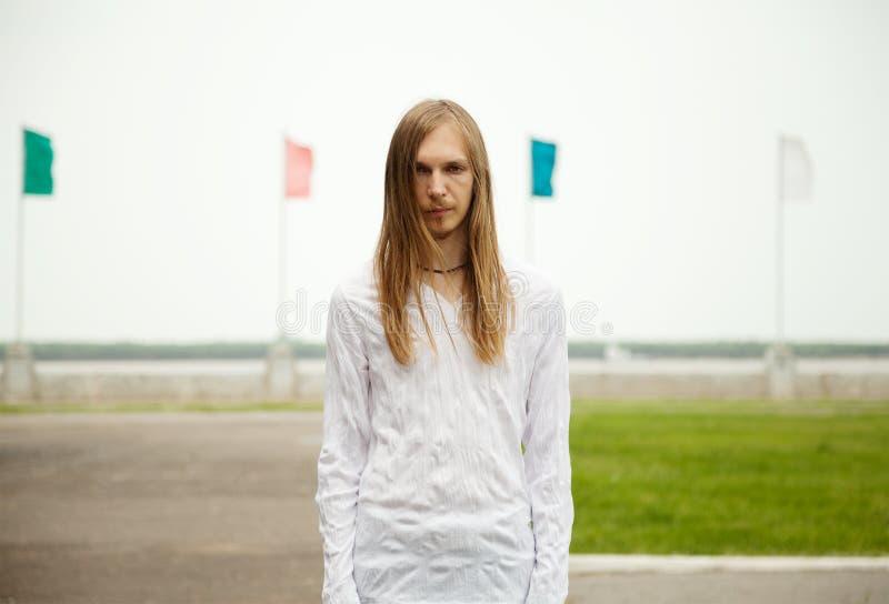 Jeune homme blond avec de longs cheveux et visage sérieux regardant fixement vous Scène tranquille paisible photos libres de droits
