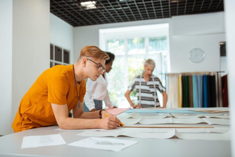 Jeune homme blond beau rédigeant un modèle de couture images libres de droits