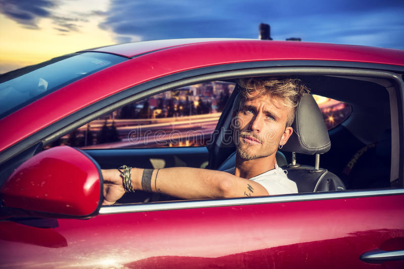 Jeune homme blond beau s'asseyant dans sa voiture photos libres de droits