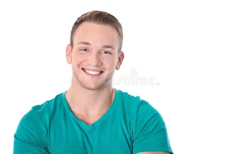Jeune homme blond d'isolement heureux dans le sourire vert de chemise : pièce en t blanche images libres de droits