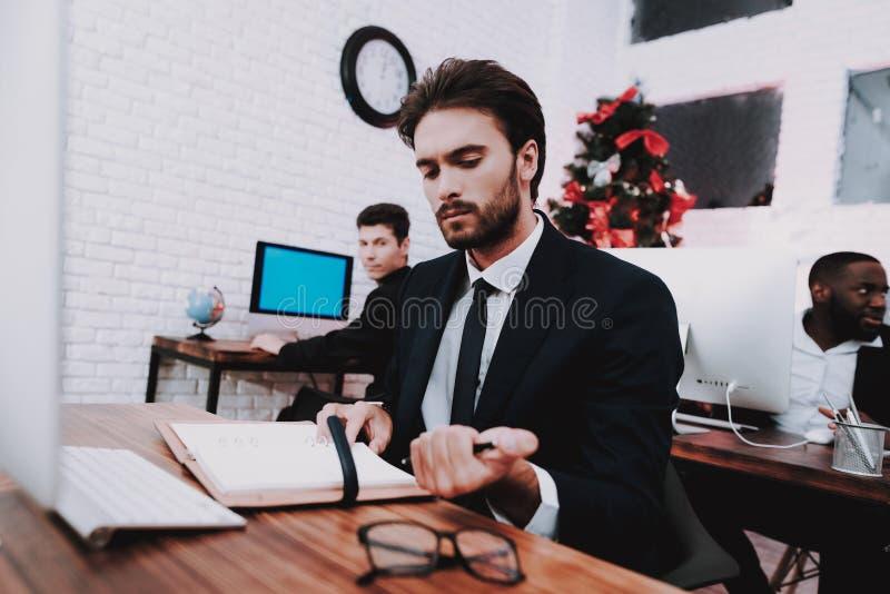 Jeune homme bouleversé travaillant dans le bureau la soirée du Nouveau an photographie stock libre de droits