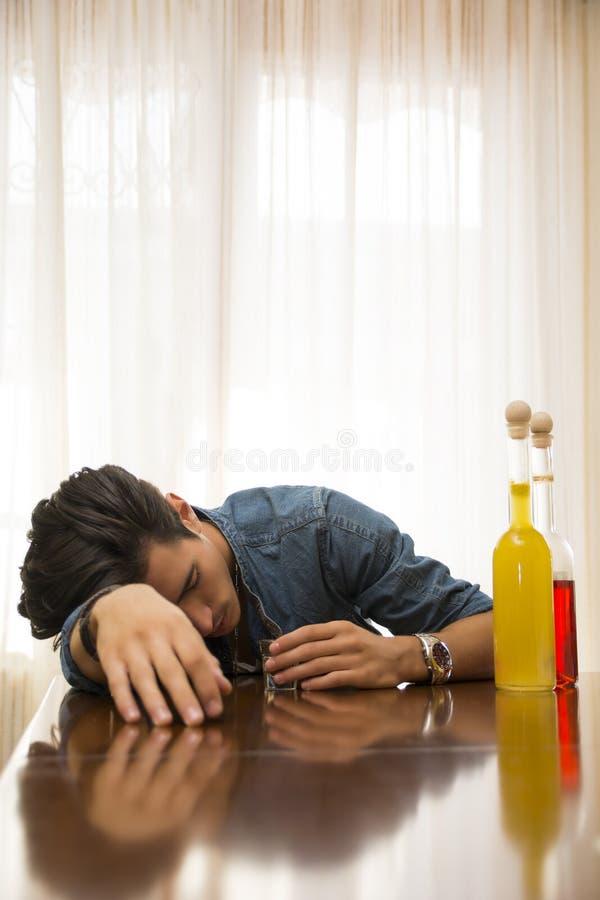 Jeune homme bu et seul dormant à une table avec deux bouteilles de boisson alcoolisée image stock
