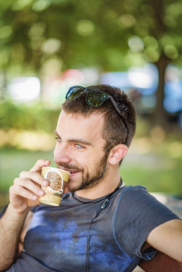 Jeune homme buvant du café soluble en parc image stock