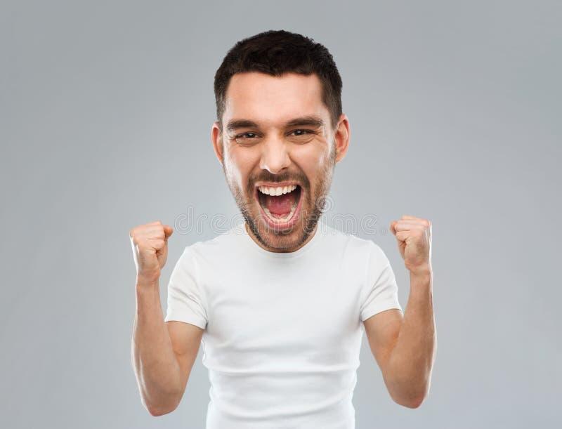 Jeune homme célébrant la victoire sur le gris image stock