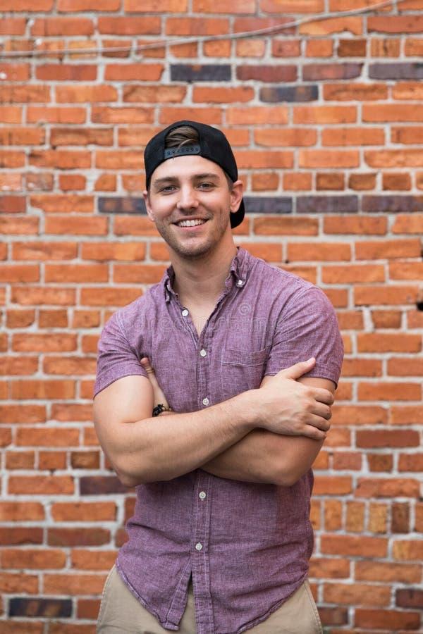 Jeune homme caucasien beau avec le téléphone portable et vers l'arrière le chapeau souriant pour des portraits devant l'extérieur photo libre de droits