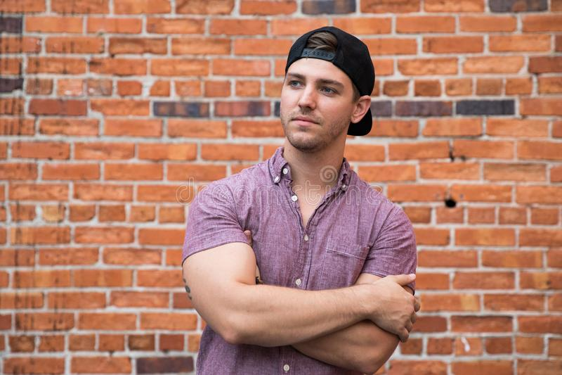 Jeune homme caucasien beau avec le téléphone portable et vers l'arrière le chapeau souriant pour des portraits devant l'extérieur images stock