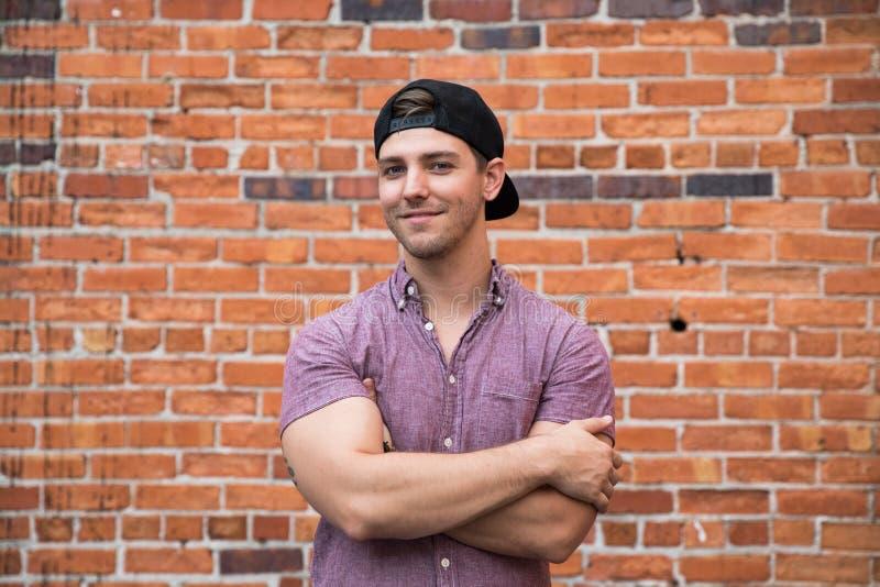 Jeune homme caucasien beau avec le téléphone portable et vers l'arrière le chapeau souriant pour des portraits devant l'extérieur photographie stock