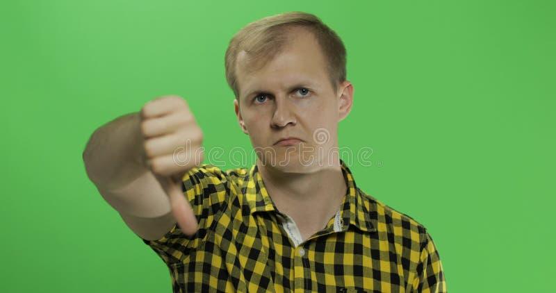 Jeune homme caucasien dans la chemise jaune ne montrant non et donnant son pouce vers le bas photos stock