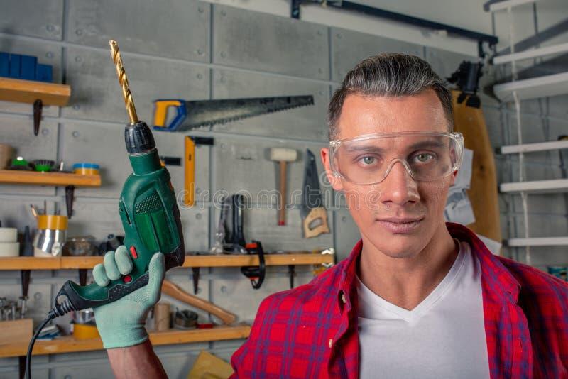 Jeune homme caucasien de sourire beau dans la chemise de plaid, verres d'oeil de sécurité dessus pour la protection, gants forant photos libres de droits