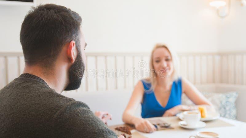 Jeune homme caucasien devant la femme passant le temps dans le café image libre de droits