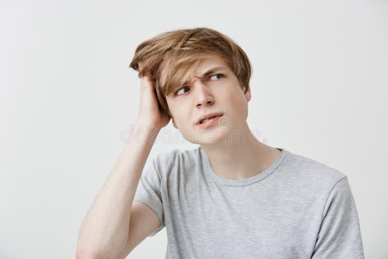 Jeune homme caucasien perplexe naïf dans le T-shirt gris regardant de côté avec l'expression confuse et perplexe, rayant photo libre de droits