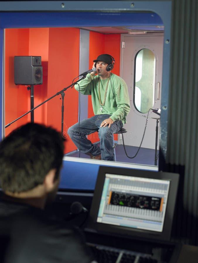 Jeune homme chantant avec le technicien In Foreground de studio images libres de droits