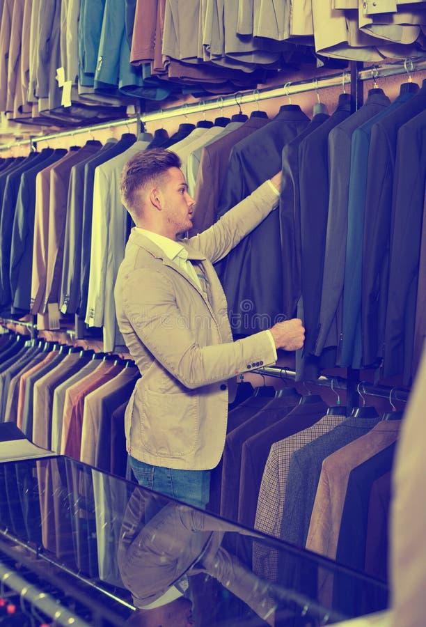 Jeune homme choisissant le nouveau costume dans le magasin de tissus de men's photos libres de droits