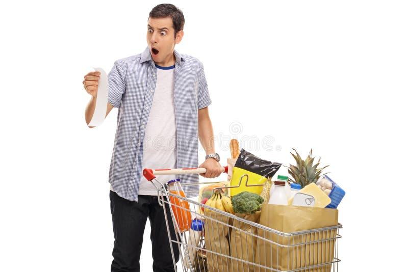Jeune homme choqué regardant un reçu de magasin images stock