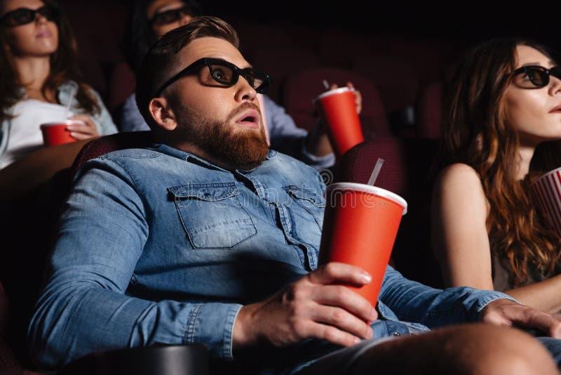 Jeune homme choqué s'asseyant en film de montre de cinéma photographie stock