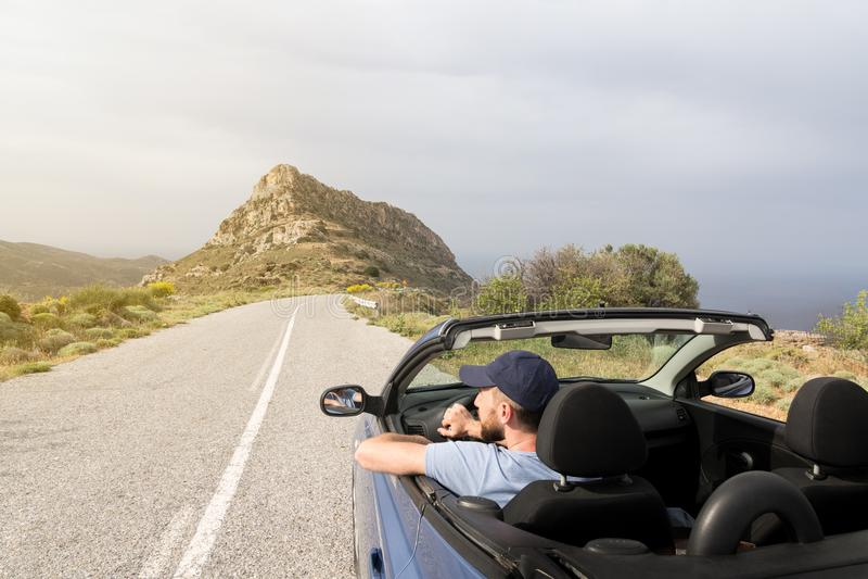 Jeune homme conduisant la voiture de location bleue convertible sans toit sur la route de montagne en île de Naxos, Grèce photo libre de droits