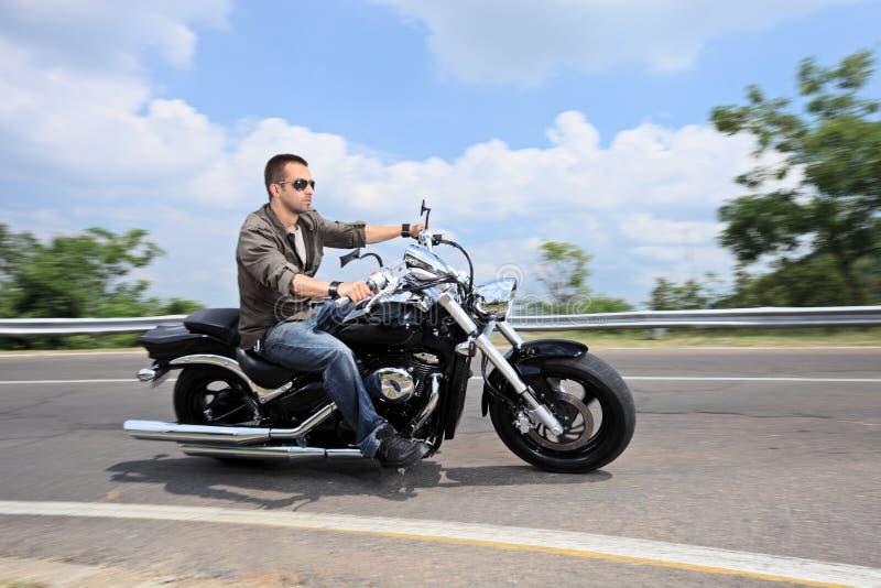 Jeune homme conduisant une moto sur une route ouverte photos stock