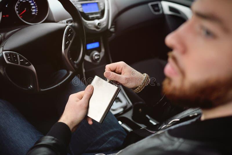 Jeune homme conduisant une voiture avec un flacon de fer photographie stock libre de droits