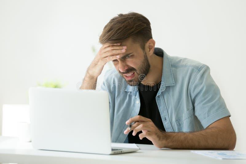 Jeune homme confus frustré par le problème en ligne regardant le lapto photographie stock