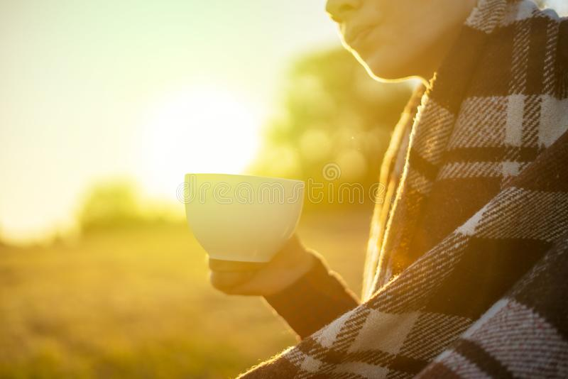 Jeune homme congelé dans le thé potable couvrant chaud se reposant dans le domaine pendant le sunet f images libres de droits