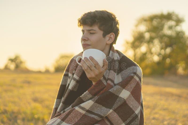 Jeune homme congelé dans le thé potable couvrant chaud se reposant dans le domaine pendant le sunet f photos stock