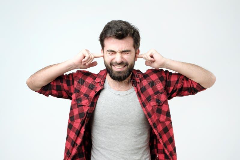 Jeune homme contrarié branchant des oreilles avec des mains Pousse de studio image stock